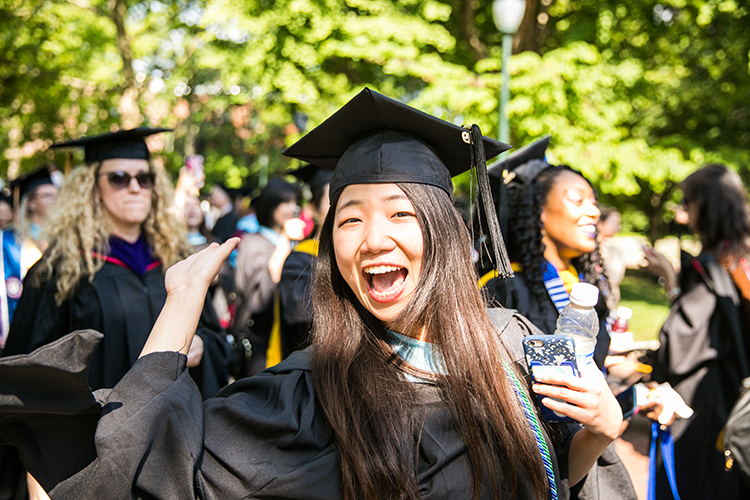 caption: A proud Penn graduate waves on her way to Franklin Field.