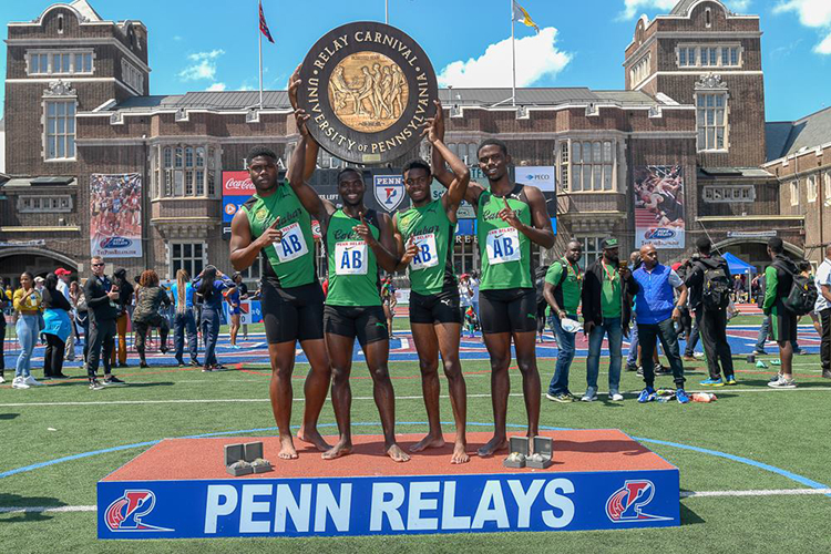 caption: Winners with the Penn Relays Wheel, designed in 1925 and depicting Ben Franklin seated, holding a laurel sprig in his left hand and greeting four runners.