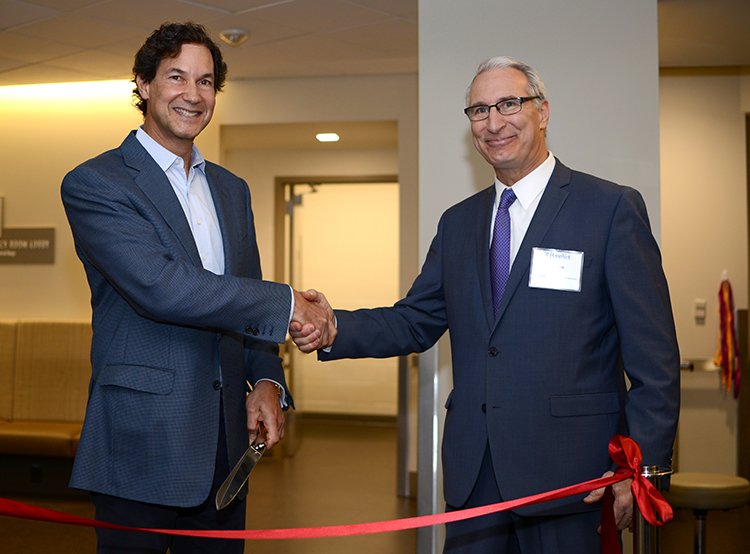 caption: Richard Lichter and Dean Andrew Hoffman cut the  ribbon at the dedication of the new ER at Ryan Hospital.