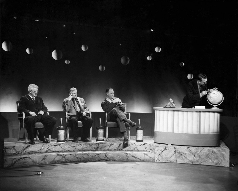 caption: Carleton Coon, Jacques Lipchitz, Alfred Kidder II and Froelich Rainey, pointing at globe, on the TV set of What in the World?